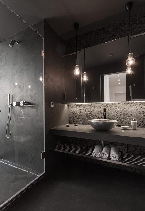 luxusbad in schwarz mit glastrennwand zur dusche, gemusterte wandgestaltung, länglichem spiegelschrank mit indirekter beleuchtung der waschtisch aus beton