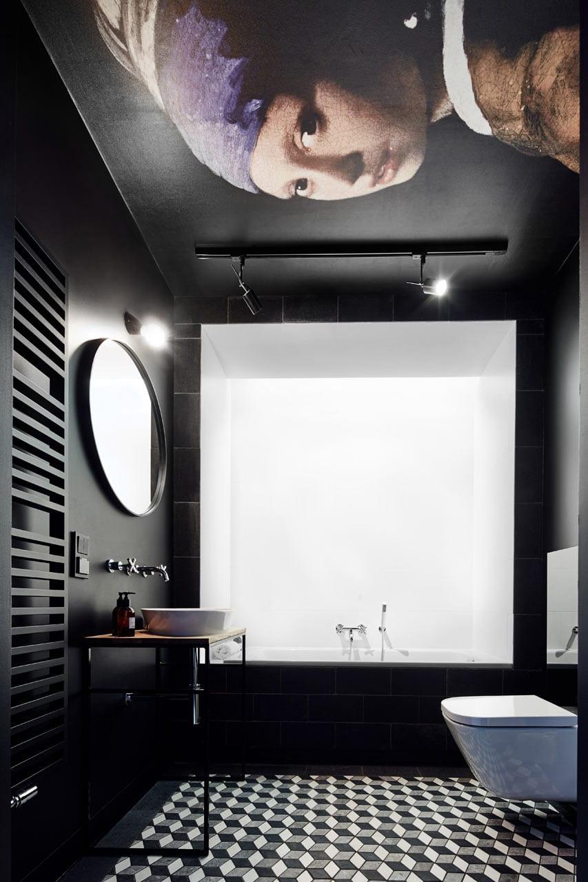 kreative badgestaltung mit schwarzen wänden und metallwaschtisch mit holztischplatte, durschbereich in weiß und kreative deckengestaltung mit gemälde