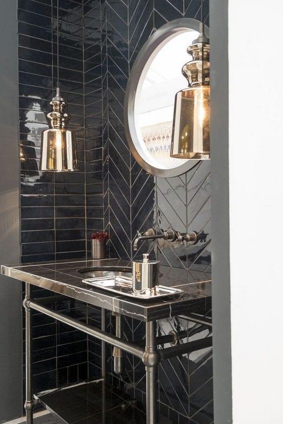 kleines luxusbad gestalten mit schwarzen badfliesen im glanz, pendellampen aus glas, metall-waschtisch und runddem wandspiegel in metallrahmen