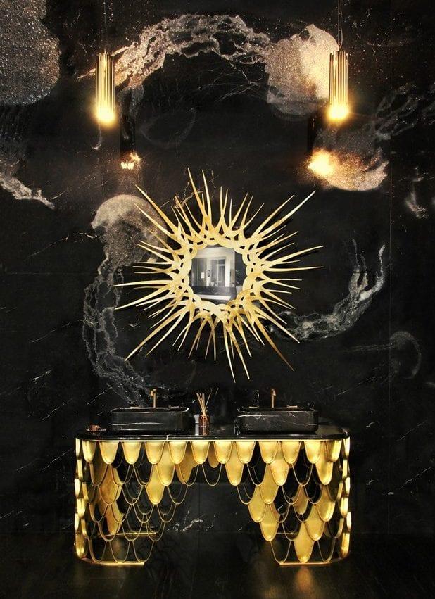 luxusbad gestaltungsideen in schwarz und gold mit wandaus schwarzemmarmor, designer wandspiegel in sonnenform und modernem waschtisch gold mit schwarzen Aufsatzwaschbecken