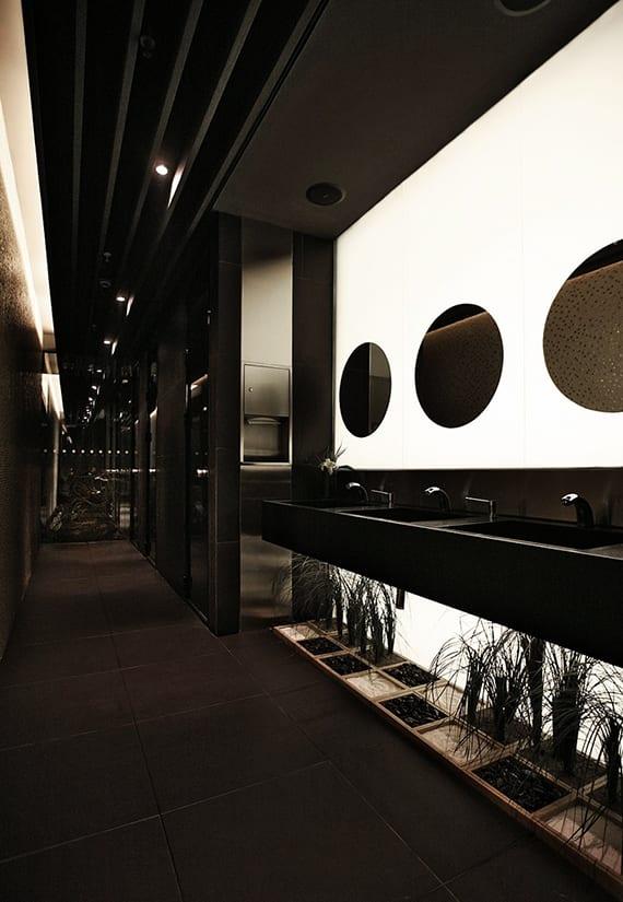 luxuriöse raumgestaltung in schwarz für moderne bäder und toiletten mit beleuchteter glaswand, schwarzer waschtisch, runden wandspiegeln und kleinem garten
