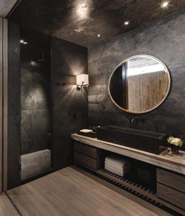 moderne bäder mit schwarzen wänden und holzeinrichtung_luxusbad mit schwarzen steinfliesen, wandspiegel rund, holzwaschtisch mit schwarzem rechteckigen waschbecken und deckeneinbauleuchten
