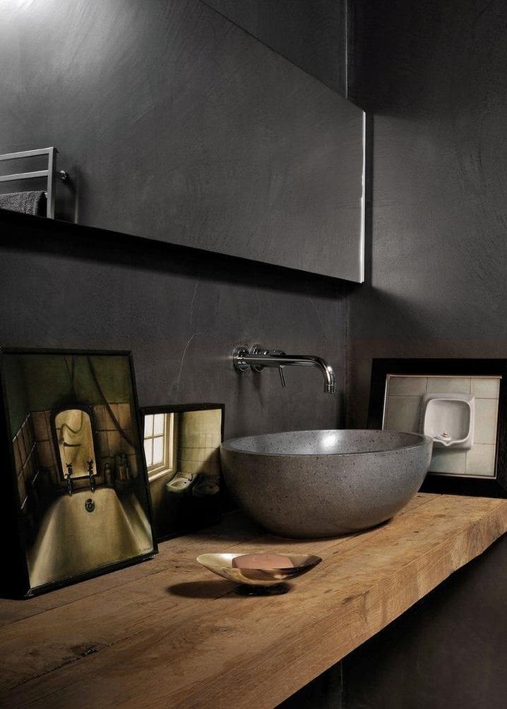 modernes bad mit schwarzen wänden, länglichem badspiegel und holzwaschtisch mit stein-aufsatzbecken und bilderdekoration