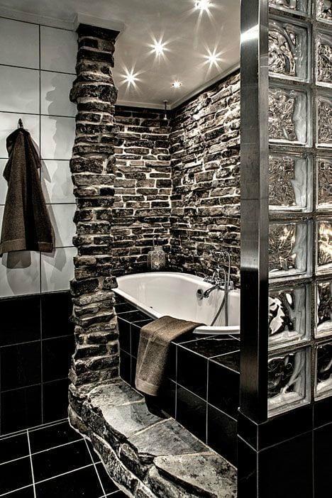 coole badgestaltung mit schwarzen und weißen badfliesen, grauer steinmauer um eingemauerter badewanne und trennwand aus glasziegeln