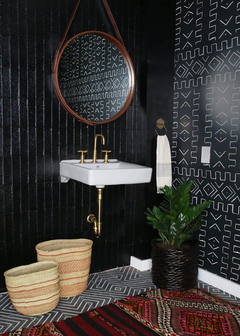 interessante badgestaltung mit schwarzer wandtapete, rundem spiegel in lederrahmen, buntem teppich und weidenkörben