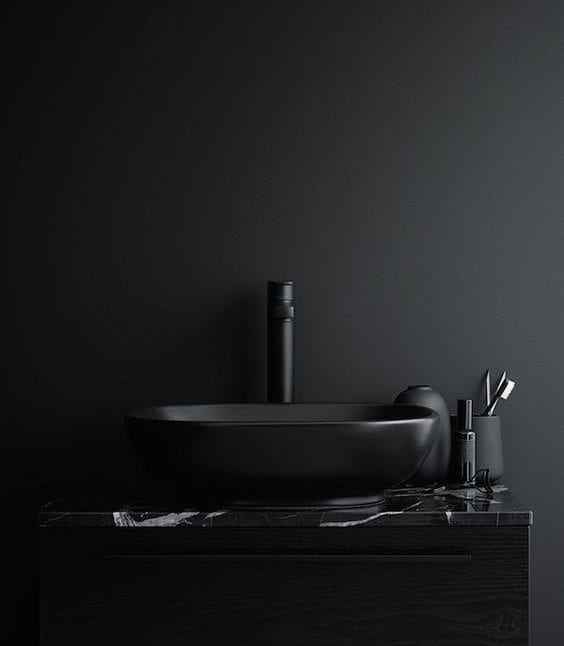 luxuriöse badgestaltung mit wandfarbe schwarz, schwarzem holzwaschtischschrank mit marmorplatte und aufsatzwaschbecken mit wasserhan in schwarz