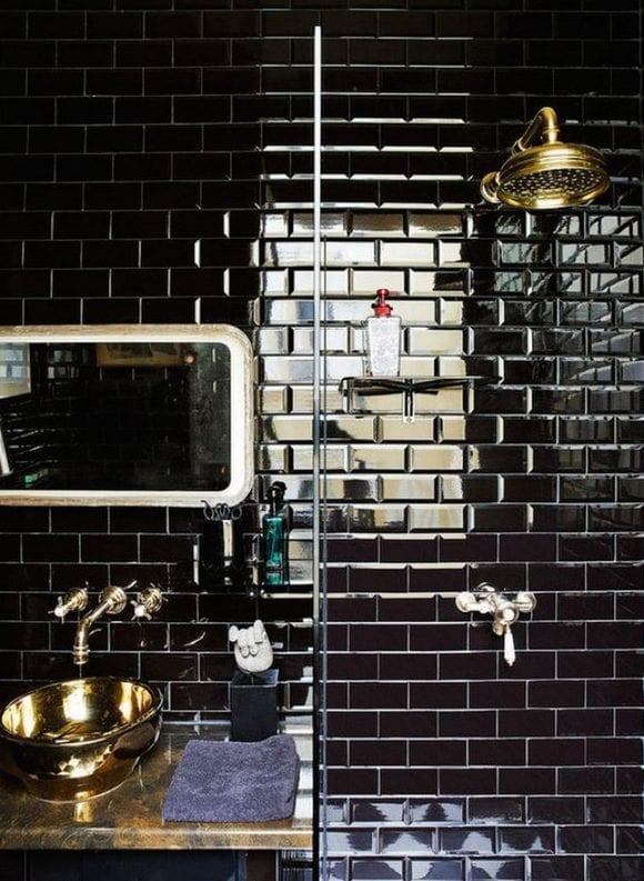 kreative badgestaltung mit schwarzen-ziegelfliesen, naturstein-waschtisch mit goldenen waschbecken und badarmatur