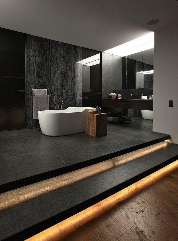 luxuriöse badgestaltung in schwarz für moderne bäder mit indirekter treppen und deckenbeleuchtung, akzentwand aus schwarzem naturstein und schwarzen glastüren