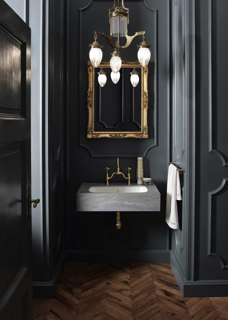 moderne badgestaltung für moderne bäder im klassischen stil mit schwarzen wänden und wandornamenten, parkettboden, waschbecjen aus acrylstein und goldenen pendellampe und badspiegel