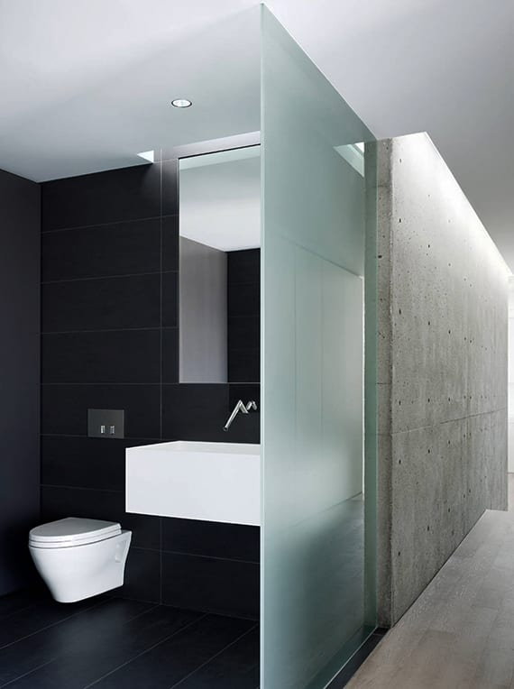 moderne badgestaltung mit großen badfliesen schwarz, glaswand, oberlicht und modernem waschbecken weiß