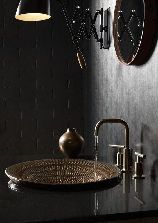 moderne badgestaltung mit schwarzen ziegeln, und schwarzem waschtisch aus naturstein mit rundem waschbecken und wasserhan in kupferoptik, rundem wandspiegel und scherenlampe