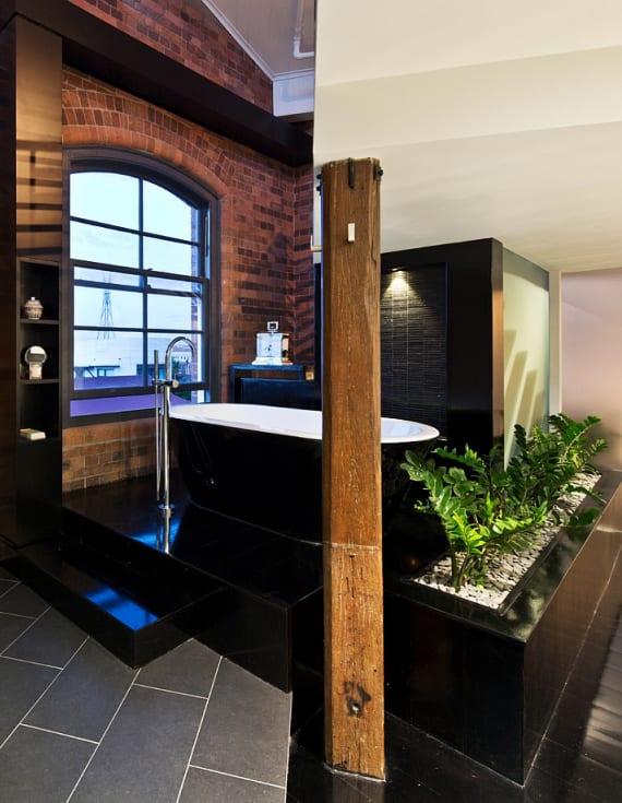 coole badgestaltung idee mit freistehender badewanne auf podest in schwarzlack, frischen pflanzen und ziegelwand mit bogenfenster