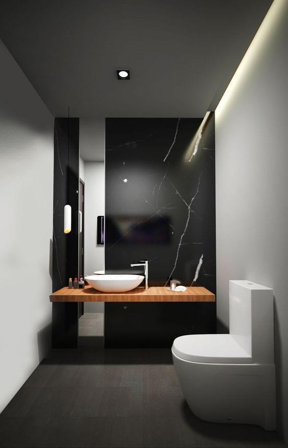 badgestaltung idee für minimalistisches bad mit schwarzer akzentwand aus marmor, raumhohem badspiegel hinter holzwaschtisch mit weißem aufsatzwaschbecken und indirekter deckenbeleuchtung