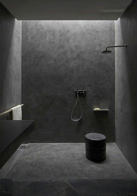 minimalistische badgestaltung mit schwarzem beton und indirekter deckenbeleuchtung