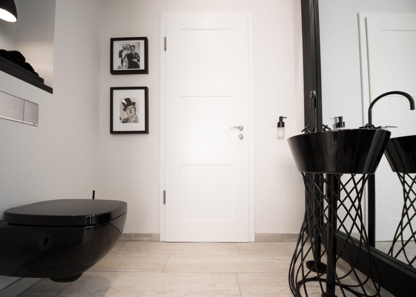 moderne badgestaltung mit schwarzer einrichtung, weißen wänden und spiegelwand mit schwarzem holzrahmen