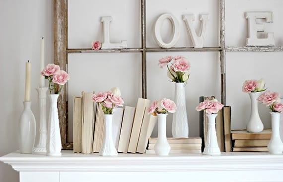 stilvolle dekoideen für rustikale dekoration in weiß mit holzfensterrahmen, büchern und weißen vasen mit rosafarbigen blumen