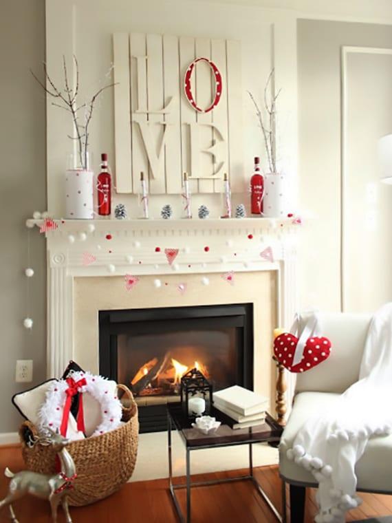 der weiße kamin romantisch dekorieren mit glasflaschen, zweigen, zapfen und DIY love-bild aus paletten