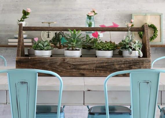 rustikale dekoidee mit fettpflanzen in holzkiste für moderne küche im vintage stil mit holzesstisch weiß und metallstühlen blau