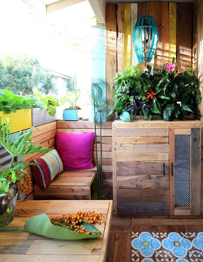 frische und bunte balkon gestaltungsidee mit wandverkleidung und bodenbelag aus paletten, diy holzschrank aus paletten und bunten blumenkübeln und dekokissen