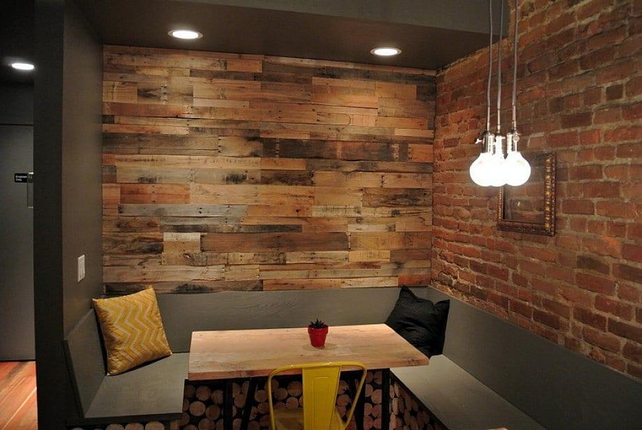 coole farbgestaltung und einrichtung kleiner küche mit essbereich_kaminholzspeicher-sitzbank grau mit holzesstisch und gelbem stuhl als akzent zu der roter ziegelwand und der wandverkleidung aus paletten