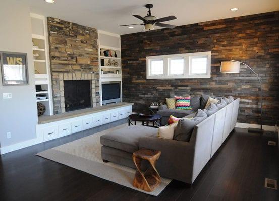 kleines wohnzimmer modern gestalten mit akzentwand aus dunklem holz, ecksofa grau mit rundem couchtisch schwarz auf weißem teppich und dunklem holzbodenbelag, einbauregale und kaminmantel aus naturstein, wandfarbe hellgrau und weiß