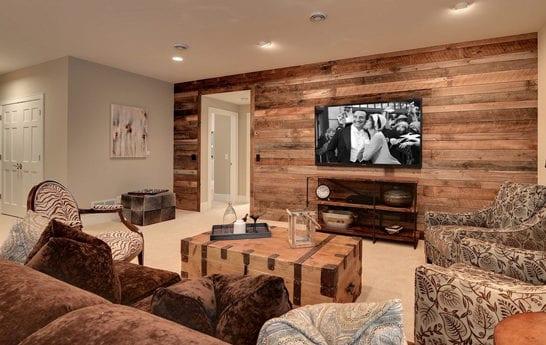 modernes wohnzimmer design mit wandverkleidung aus brettern, braunem sofa aus plüsch, holzkiste als couchtisch und stühl mit zebramuster