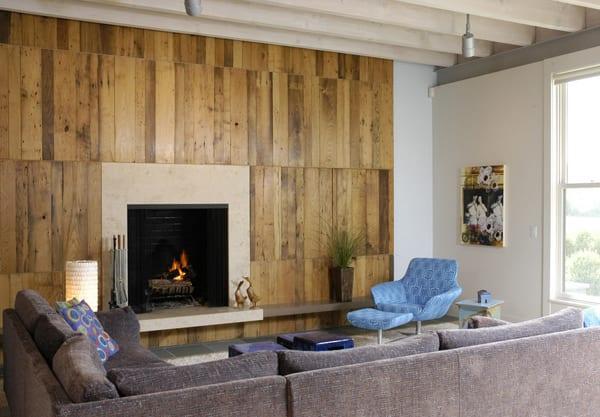 modernes wohnzimmer mit wandkamin, wandverkleidung aus vertikalen holzbrettern, sichtbaren holzbalken und ecksofa dunkelgrau