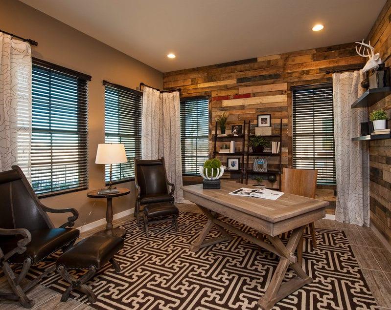 cooles Homeoffice Interieur Design mit holzschreibtisch, vintage Sesseln mit Hocker aus Leder, schwarzweißem Teppich, weiße gardienen und schwarzen Bücherregalen aus metall auf holzwand