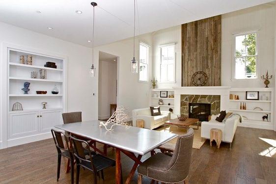 modernes wohn-esszimmer mit parkett, weiß gestrichenen wänden und einbauregalen, kamin mantel aus steinen und holz mit regal