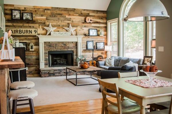 wohnesszimmer mit parkett, paletten-akzentwand mit kamin aus naturstein, rustikale küche mit hozbar, holzesstisch mit holzstühlen und sofa mit metallcouchtisch auf weißem teppich