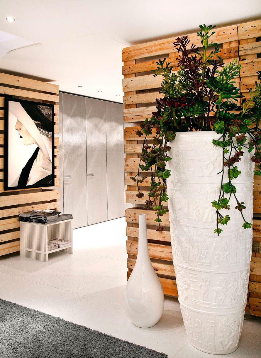 originelle Raumgestaltung mit europaletten als wandverkleidung, weißem fußbodenbelag und großen Blumenvasen weiß
