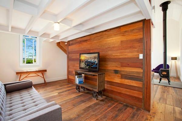modernes interior design im industrialen stil mit trennwand holz zwischen küche und wohnzimmer, parkett, hängekamin schwarz, modernem sofa grau, vintage tv regal auf rollen und rippendecke weiß