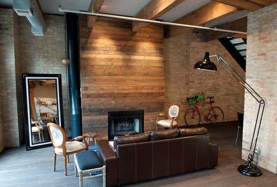 moderne wohnung mit wänden aus weißen ziegeln, kamin mit mantel aus holz, holzträger und vintage stehlampe schwarz