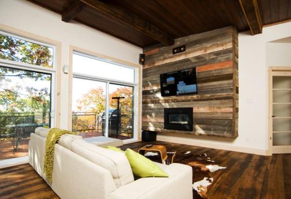 moderne wohnung mit holzdecke und holzfußboden, weißen wänden und selbstgebauter TV-Wand aus holzbrettern, sofa weiß und kuhfellteppich