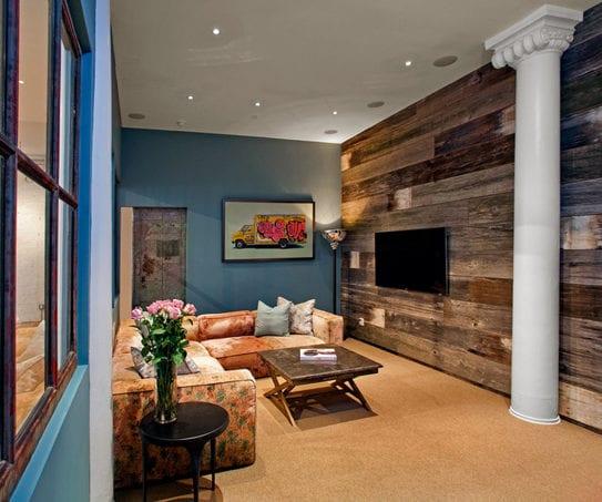 kreative gestaltungsidee fpr kleine wohnzimmer mit tv wand aus holzbrettern, wandfarbe blau, runder säule weiß und ecksofa in orange mit blumenmuster