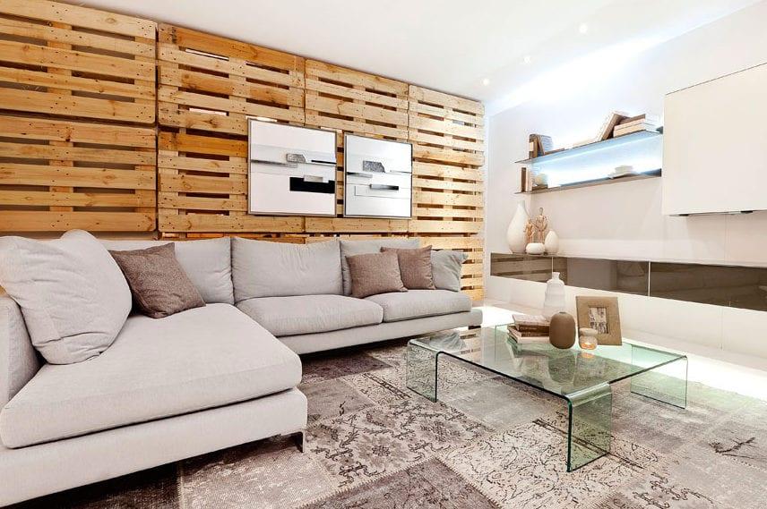 modernes wohnzimmer interior mit Akzentwand aus paletten, ecksofa grau, glas couchtisch auf teppich grau und moderner wohnwand