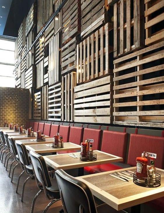 cooles interioir design mit wandverkleidung aus europaletten, ziegelwand, schwarzer sitzbank mit roten polstern und holzesstischen