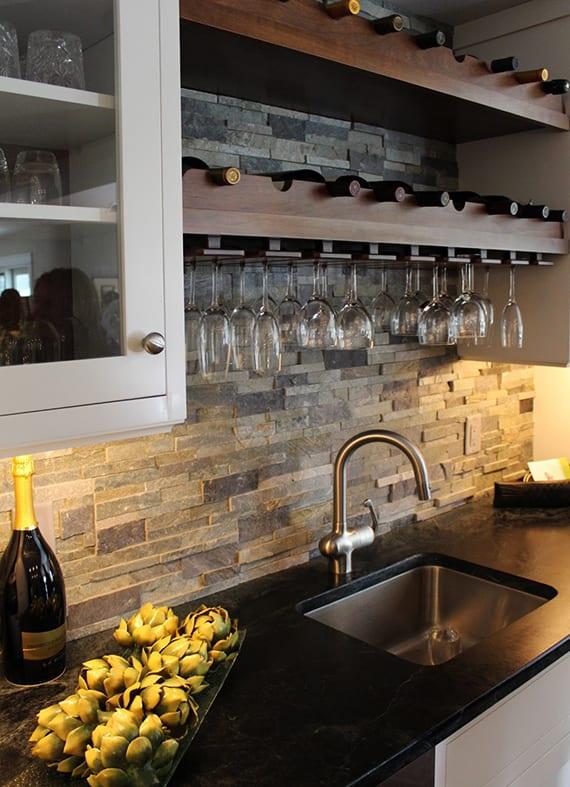 küche gestalten mit akzentwand aus naturstein, weißen küchenschränken mit glastüren und modernem wandregal für weinflaschen und weingläser