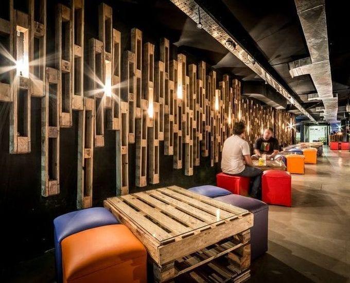 minimalistisches interior mit betonboden, schwarzer wand mit diy deko und Wandleuchten aus Paletten und coole DIY Paletten-Tische mit bunten polsterhockern