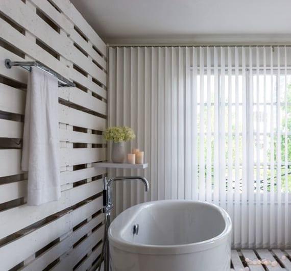 coole badezimmer ideen für einrichtung mit paletten im bad_ modernes bad weiß mit bodenbelag und wand aus paletten, badewanne freistehend und lamellenvorhang weiß