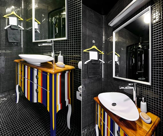 moderne und kreative badgestaltung mit schwarzem mosaik, badezimmerspiegel im weißen rahmen, klassischem waschtischschrank mit streifen