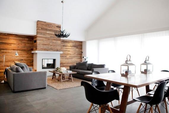 modernes wohnesszimmer mit kamin,betonboden, Akzentwand aus Holz, zwei grauen Sofas mit holzcouchtisch und esszimmertisch aus holz mit schwarzen stühlen