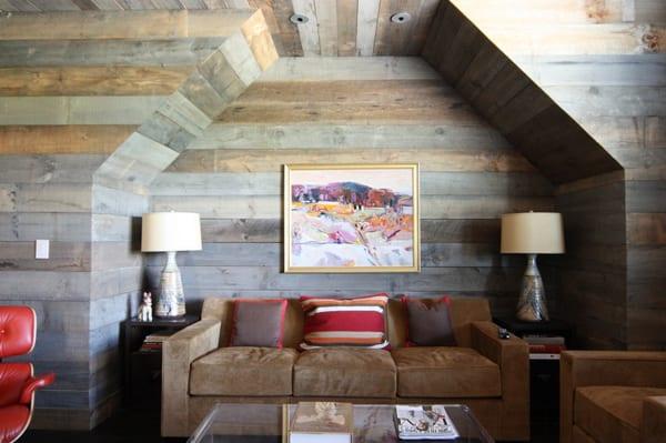 kleines wohnzimmer platzsparend einrichten durch sofa mit zwei beistelltischen und tischlampen in wandnische mit holzwandverkleidung in grau
