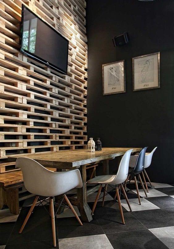 kreative raumgestaltung und modernes interieur design mit schwarzen wänden, europaletten und bodenfliesen in schwarz und weiß