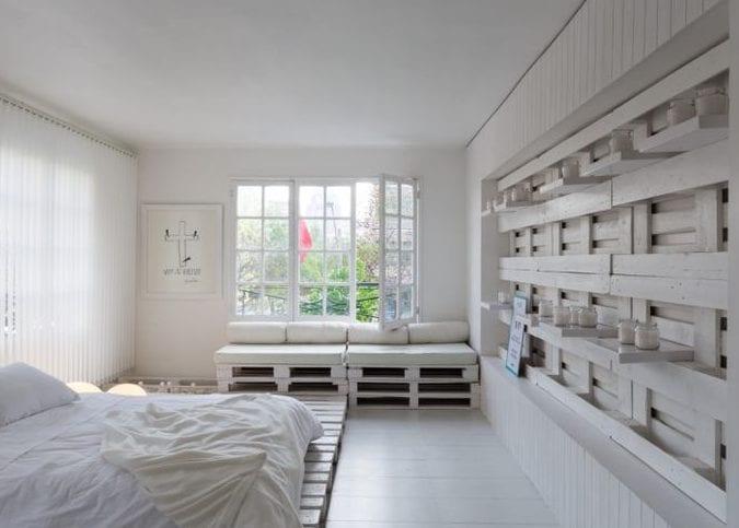 weißes schlafzimmer gestalten mit weiß gestrichenen paletten, diy paletten-Sofa mit weißen kissen und diy wandregalen mit weißen kerzen