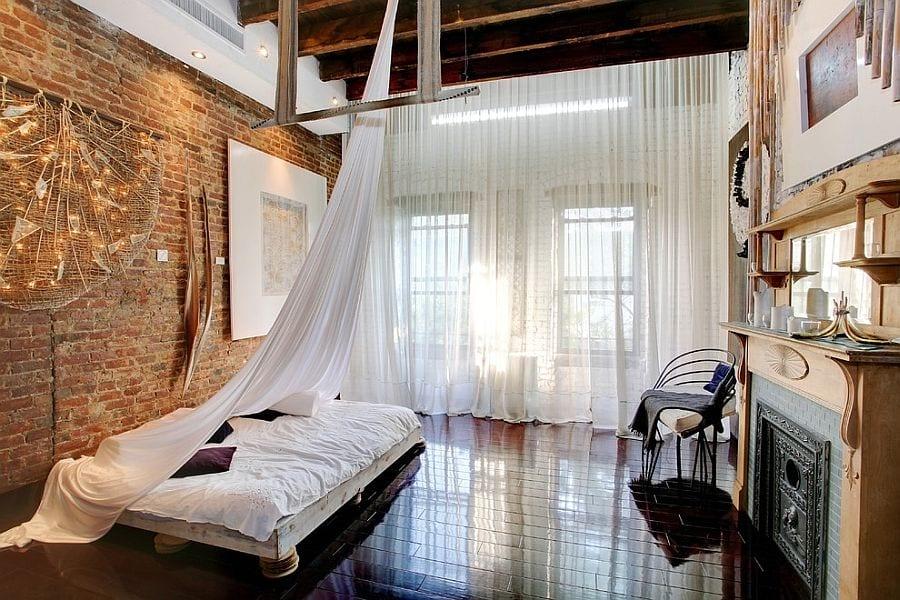 modernes schlafzimmer gestalten mit akzentwand aus ziegeln, holzdeckenbalken, schwarzen bodenfliesen, weißen gardinen und kamin mit regal