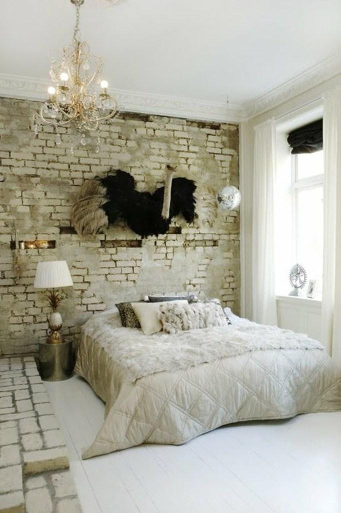 kleines schlafzimmer in weiß originell gestalten mit weißer ziegelwand, kronleuchter, nachtisch aus metall rund und coole strauß-wanddeko