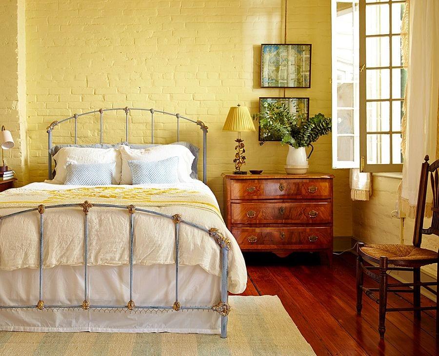 schlafzimmer gemütlich gestalten im rustikalem stil mit metallbettgestell, klassischer Kommode aus holz, ziegelwänden in hellgelb und frisches grün in weißem porzellankanne