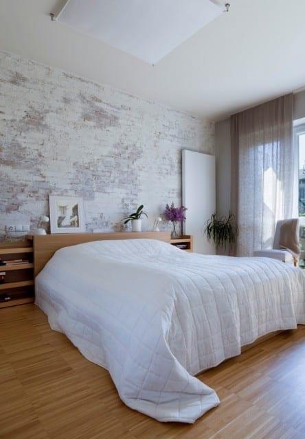 schickes schlafzimmer mit holzfußbodenbelag, bettkopfteil mit schiebbaren regalen aus holz, unverputzter Ziegelwand weiß, rechteckiger deckenlampe aus milchglas und gardinen in beige
