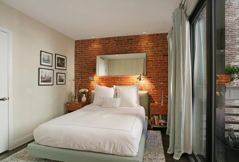 modernes schlafzimmer klein mit ziegelwand rot, polsterbett in und gardinen in hellgrün, holznachttischen, wandleuchten chrom und wandspiegel als wanddeko
